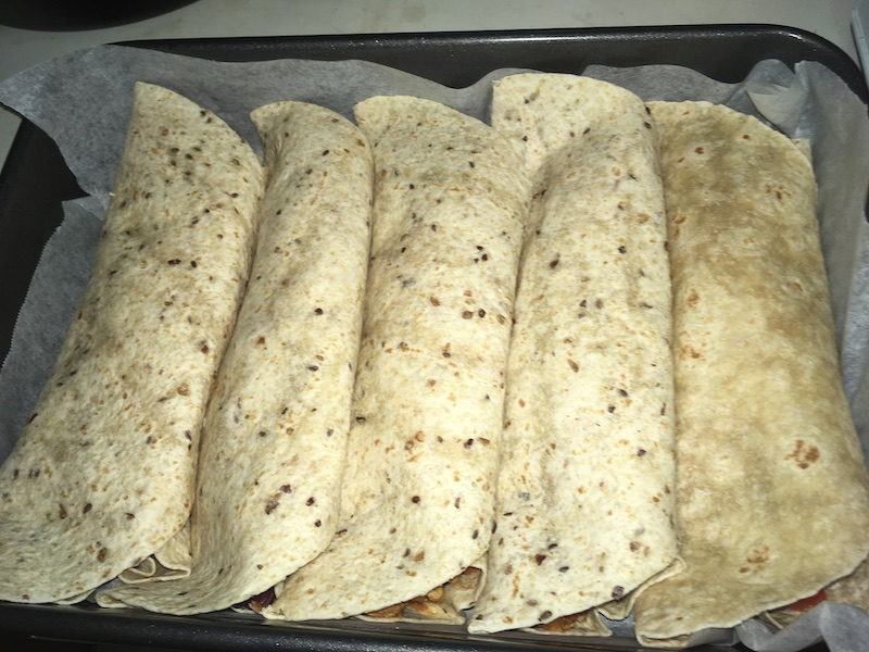 five rolled wrap breads in a roasting pan