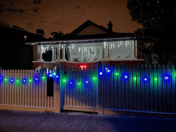 a house close to the street with bright snowflake lights and a 'Merry Christmas' light