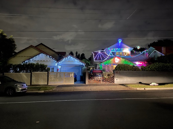 a 1920s house with white lights hanging from the eaves and colourful ones on the fence