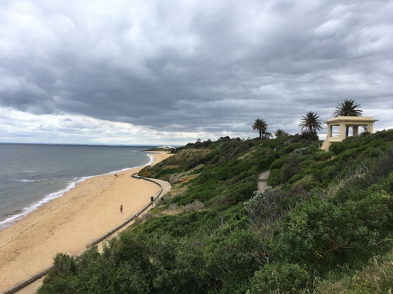 a view from a coastal cliff; greenery and a white structure to the right, sand and ocean to the left, and cloudy skies above