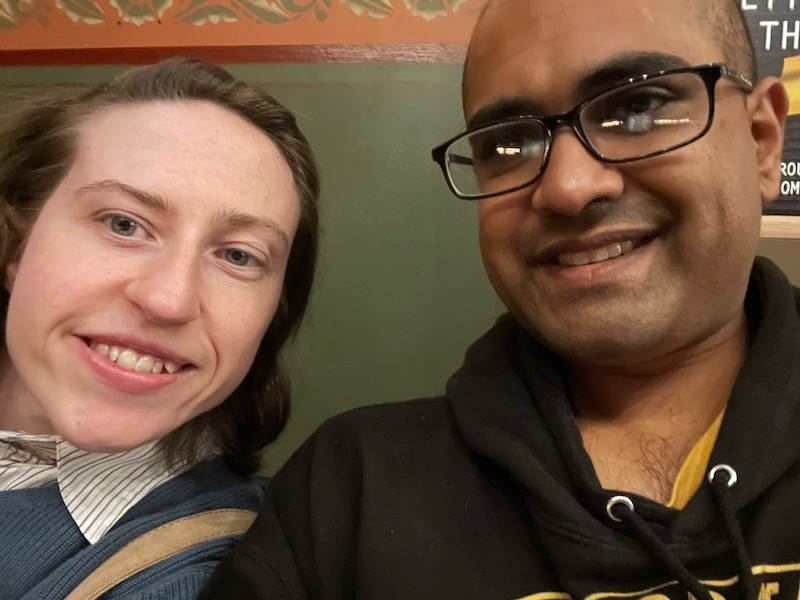 a selfie of a brunette white woman and bald bespectacled Indian man
